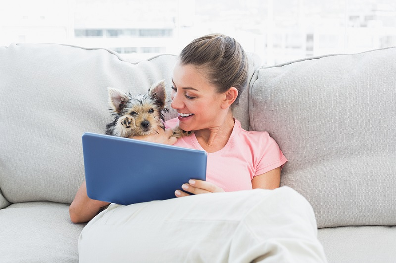 Cheerful woman using tablet with her yorkshire terrier at home i